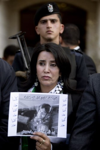 A Palestinian woman holds a poster with a picture of pilot Muath Kasasbeh during a protest in front of the Jordanian embassy in the West Bank City of Ramallah on Wednesday (AP Photo by Majdi Mohammed)
