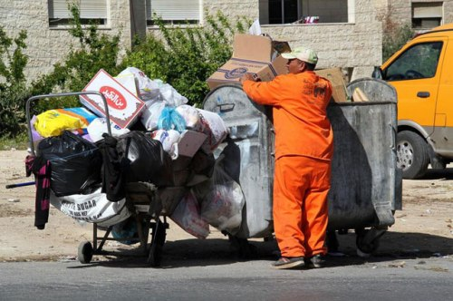 A sanitation worker disposes of trash in Amman on Monday (Photo by Osama Agarbeh)